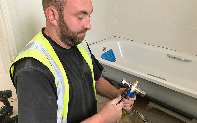 Plumber installing Thermostatic Mixing Valve