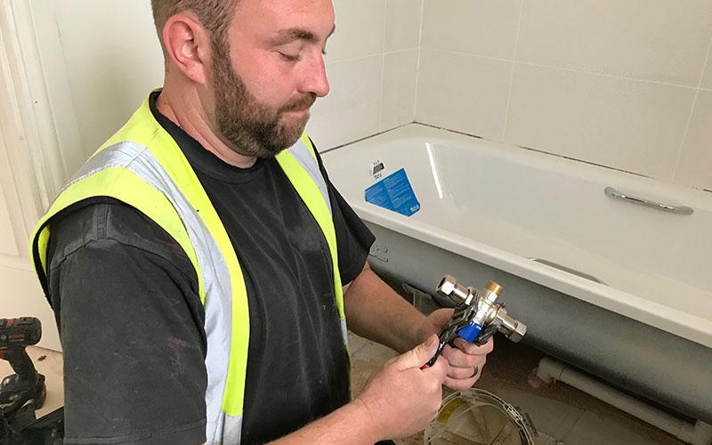 Plumbers installing a TMV under a bath