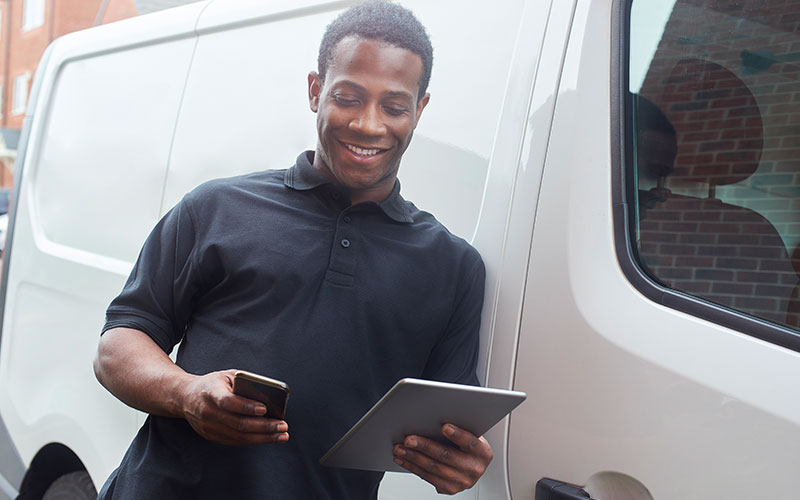 A tradesman stood at the side of his van using a digital tablet and smart phone