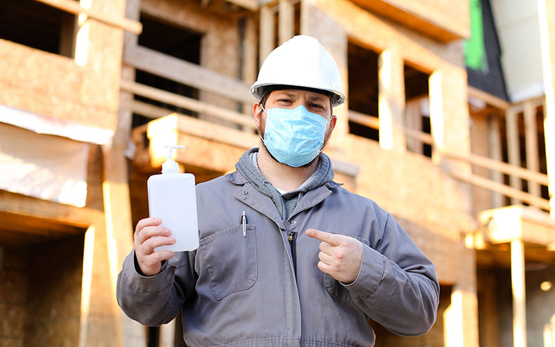 Man with a mask and hand sanitiser on a building site