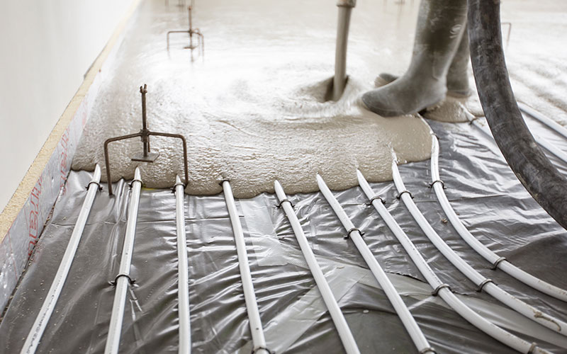 Man pouring screed on a underfloor heating installation