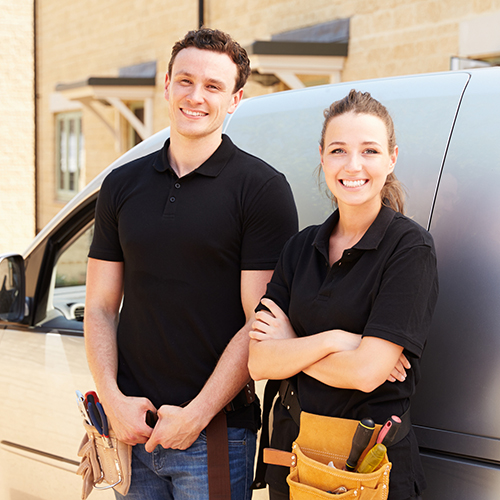 Portrait of male and female trade workers by a van thumbnail
