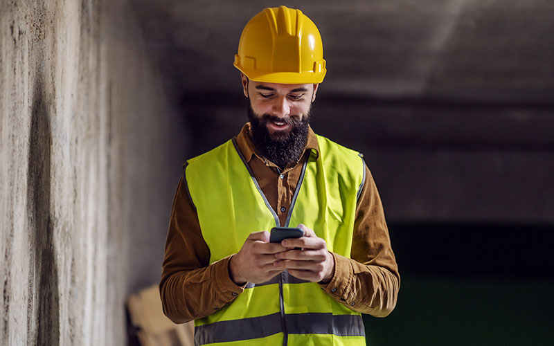 Young attractive smiling bearded worker in vest with helmet on head standing inside of building in construction process, typing a message on smart phone and taking a break from work.