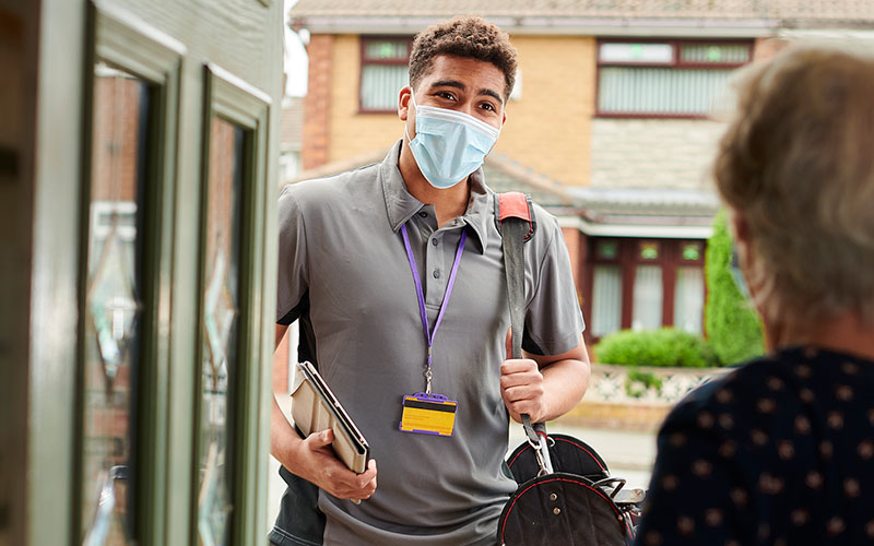 a young workman visits an elderly resident with his facemask on