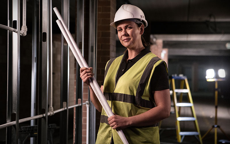 Female installer holding John Guest white pipe