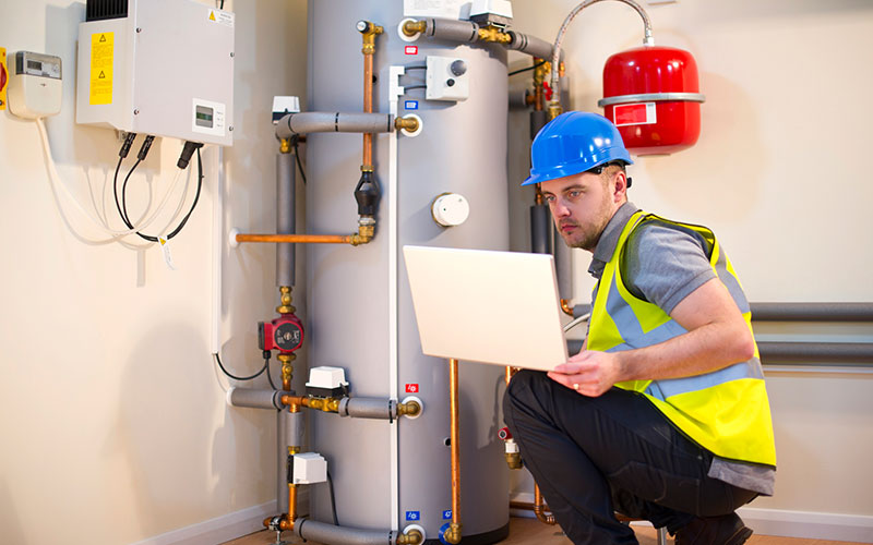 Technician checking an expansion vessel with laptop