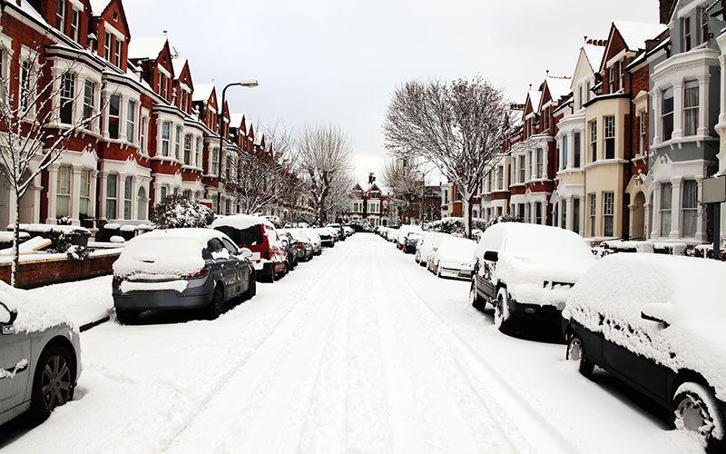 English road with cars on either side covered in deep snow