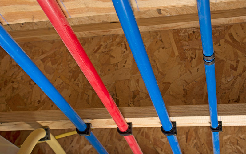 PEX pipes attached to the basement ceiling of a home, angled view.