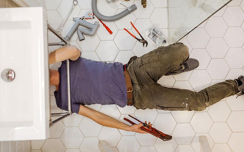 Man solving plumbing problems in his bathroom