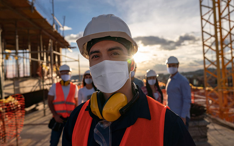 Portrait of a happy construction worker at a building site wearing a facemask with a group of workers at the background
