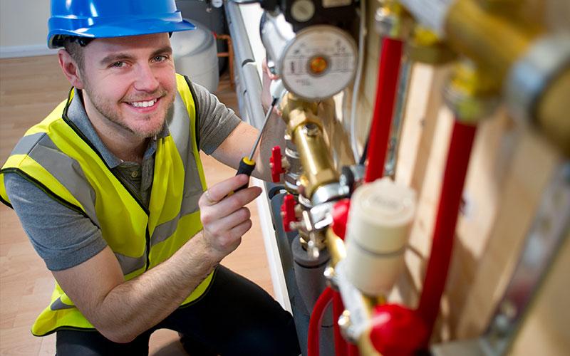 engineer installing underfloor heating system